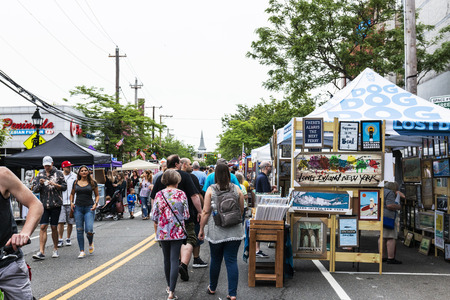 Bay Shore, New York, USA - 10 June 2018: Vendors selling artwork and goods, with people strolling on main street during a street fair in Bay Shore Long Island.