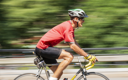New York City, USA - 15 August 2018: A man training on his racing road bike with the background blurred on a summer morning in Central Park NYC.