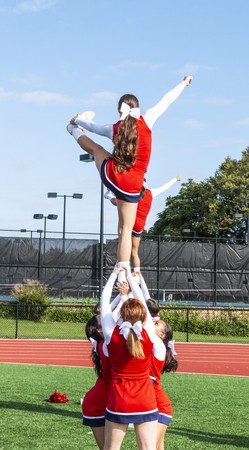 Cheerleaders in a pyramid practicing holding their teammate up by thieir ankles before homecoming. Stok Fotoğraf - 114869578