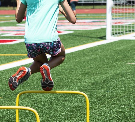 A youn girl is jumping over a two foot yellow hurdle on a green turf fielld during practice in the summer. Stockfoto