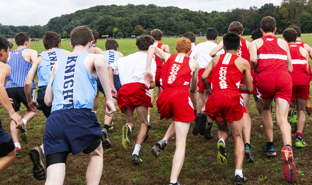 Bronx, New York, USA - 13 OCtober 2018: High school boys cross country race at the start as the boys head accross the grass to the hills in VanCortlandt Park, NY.
