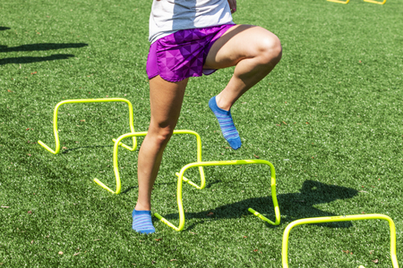 A track and field runner is not wearing shoes while performing form drills by stepping over yellow mini hurdles on a turf field in socks and shorts. Standard-Bild - 114868096