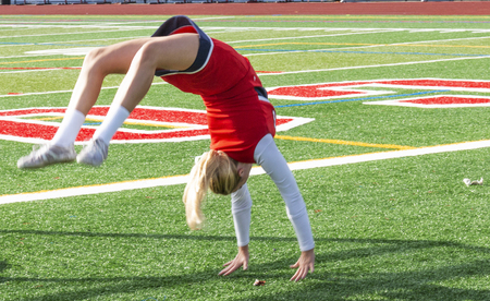 A high school cheerleader warming up doing back flips on a turf field before the game. Stok Fotoğraf - 114870812