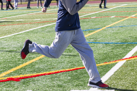 A high school sprinter is running on a green turf field during winter track and field practice.