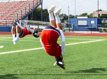 Two high school cheerleaders are practicing flips on the infield before a football game. Stok Fotoğraf - 114870818
