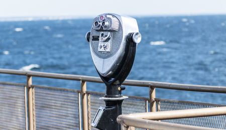 A coin operated telescope in available to look out on to the rough waters on a ferry boat in the Long Island Sound.