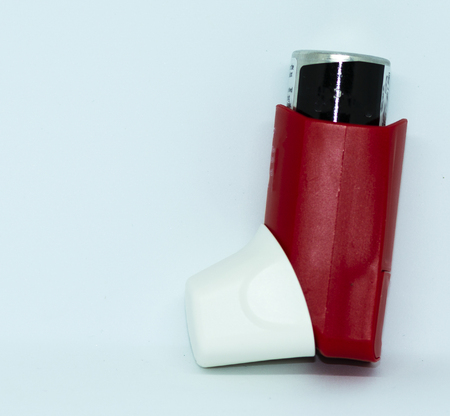 A red and white asthma rescue inhaler standing infront of a white background. Banque d'images