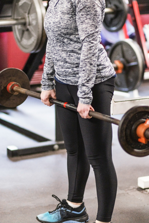 A high school track and field athlete is learning to do deadlifts in the wieghtroom.