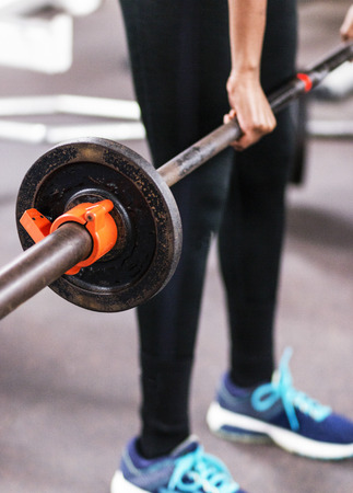 A young high school female track runner is learning how to do cleans while lifting weights in the weightroom. Stock Photo