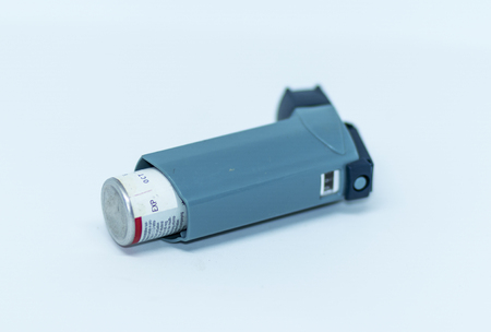 One inhaler laying on its side facing away from the camera with a white background.