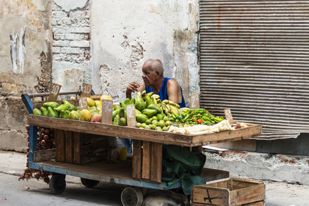 Havana, Cuba - 25 July 2018: A man sitting behind his fruit cart smoking a cigarette while selling fruit on the streets of Havana Cuba.