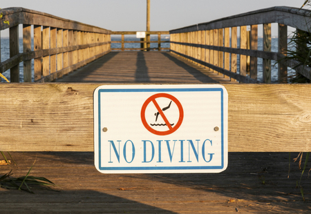 A no dving sign is nailed on to a wood pier on th coast of Long Island, New York.