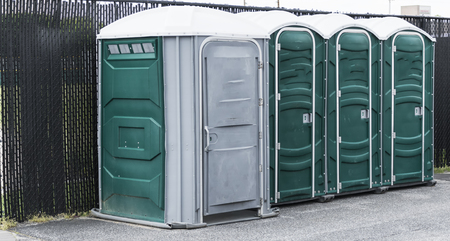 Porta potties set up in a parking lot before an event being held at a high school. Stock Photo