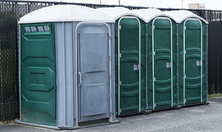 Green and gray potties set up in a parking lot with the end one for handicapped.
