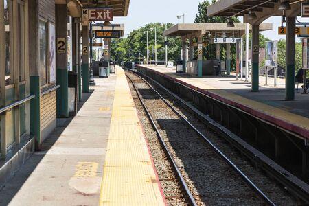 Babylon, New York, USA - 14August 2018: Babylon Railroad station platform looking west down the tracks.