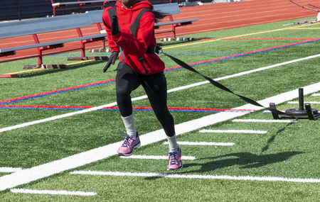 A high school female sprinter is running while pulling a sled with a twenty five pound weight on it.