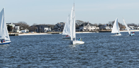 Small two person sailboats sailing around the great south bay between West Islip and Babylon, New York during a winter regatta.
