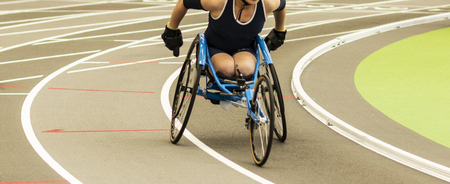 A high school girl in a wheelchair is racing the mile on an indoor track.