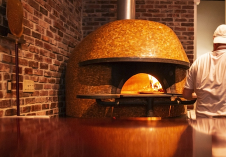 A chef is putting an uncooked pizza in to the high heat of a brick oven pizza oven. Imagens