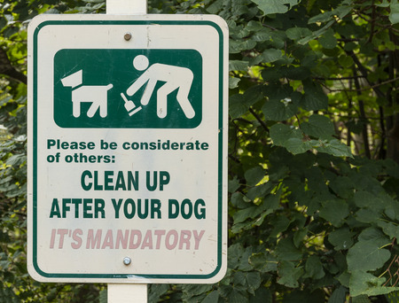 A white sign with green print is posted in a park telling people to clean up after their dog, its mandatory.