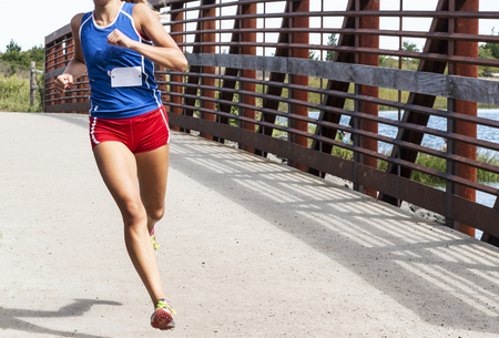 A high school cross country girl is running a race crossing a bridge wearing red shorts and blue racing top. 스톡 콘텐츠