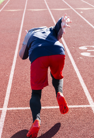 A high school sprinter is practicing the start of his race in the winter on a track. Picture taken from behind the athlete.