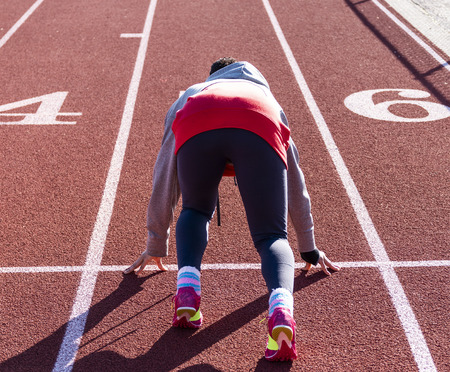 A high school teenage girl is in the set position ready to sprint down the straightway of a track during track and field practice. Stock Photo