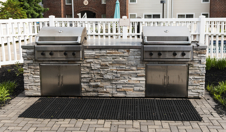 A hotel has two gas barbecue grills ready for use by patrons on vacation to gather with friends and family in the pool area.