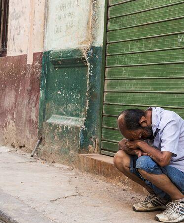 Havana, Cuba - 25 July 2018: Cuban man looks to be in dispair sitting on a ledge infront of old run down building in Old Havana Cuba.