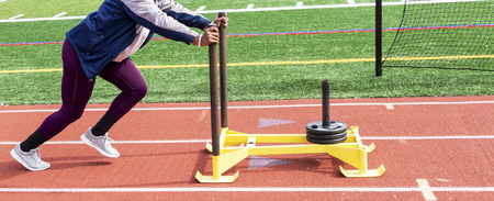 A high school shot put girl is pushing a yellow sled with seventy five pounds of weight on it down a red track.