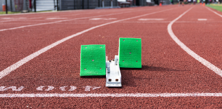 A set of green starting blocks are ready for a sprinter to run the 400 meter dash on a red track.