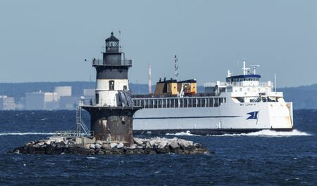 Orient Point, New York, USA - 10 October 2019: The cross sound ferry is passing the Orint Point lighthouse on a windy day in rough water. Editorial