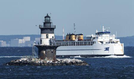 Orient Point, New York, USA - 10 ottobre 2019: Il traghetto incrociato sta passando il faro di Orint Point in una giornata ventosa in acque agitate. Editoriali