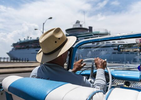 Picture of taxi driver driviing a restored convertible in Havan Cuba, passing a cruise ship, taken from the back seat of the car. Standard-Bild
