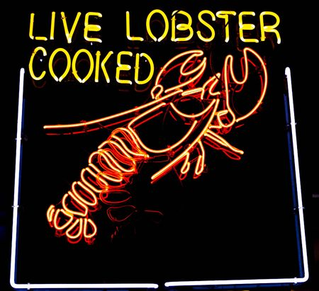 A very bright orange and yellow neon sign with a picture of a lobster that reads live lovster cooked.