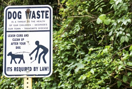 A sign on the side of the road reminding people to clean up after the dog and to have them on a leash. Banque d'images - 125328124