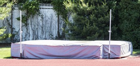 A high jump pit set up in the jumping area with a gray cover and standards.