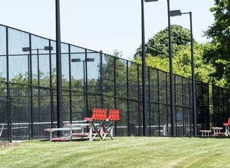 Small aluminum and plastic bleachers set up on the grass by each tennis court for spectators to enjoy the game.