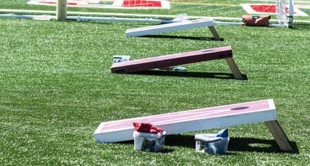 Three homeaide wooden corn hole game boards are set up side by side on a green turf field with bean bags in containers.