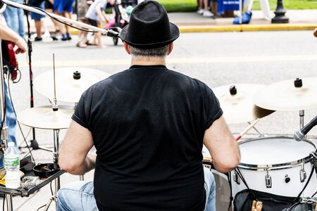 A drummer playing in a band at a street festival outdoors taken from directly behind the performer.