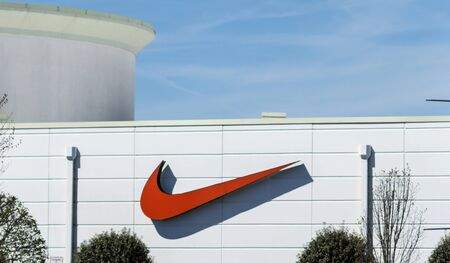 Deer Park, New York, USA - 17 April 2019: A large Nike swoosh in on the outside of the Nike Store facing the road on a white building.