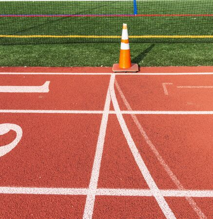 Side view showing the start and finish line marked by an orange cone on a track.