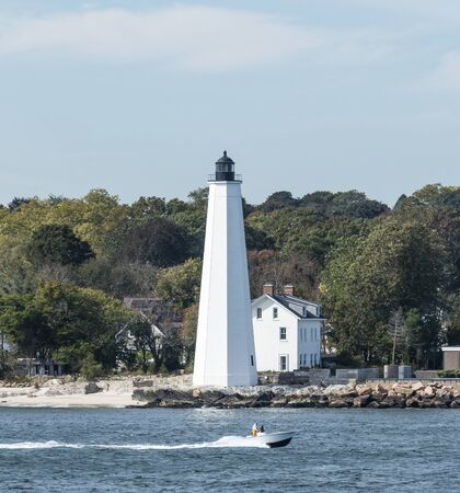 A motor boat moving in front of the New London lighthouse taken from the water.