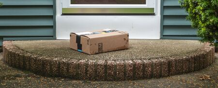 A package is delivered and placed on a wet stoop in the rain in the front of a house exposed to the elements and theft by a delevery service. Standard-Bild