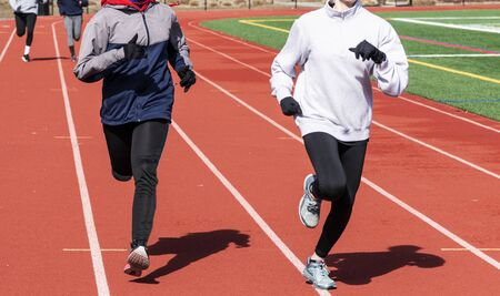 High school girls running two by two in lanes on a sunny but cold afternoon training for track and field events.