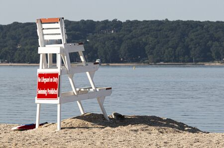 A white lifeguard stand up on the sand looking over the empty water of the north shore of Long Island with hills and trees in the backgound.
