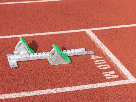 A set of track and field sprinters starting blocks with green pads, is set up at the start line in lanes of the 400 meter dash.