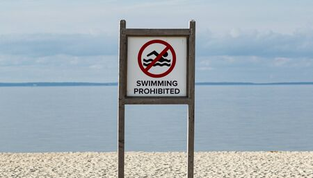 A large wood sign on the beach reads swimming prohibited wirh a calm bay in the background. Stock fotó