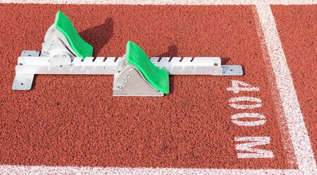 A set of track and field sprinters starting blocks are set up at the 400 meter starting line on a red track.