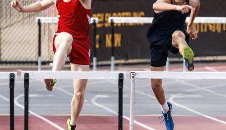 Two high school boys are tied in the 400 meter hurdle race entering the final straightway.
